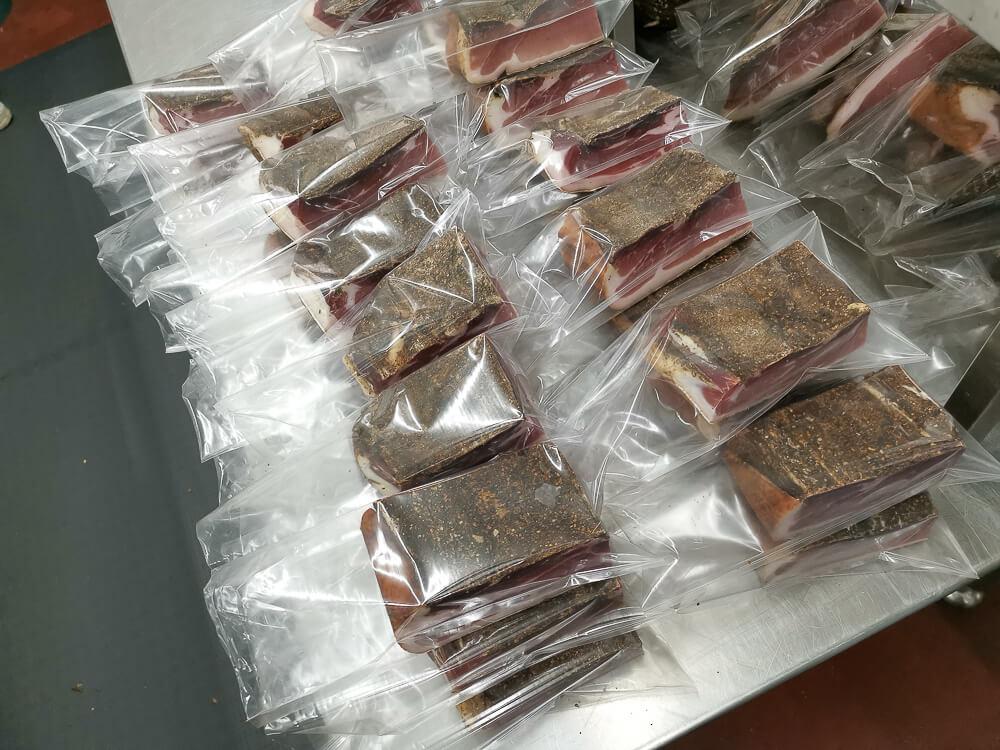 Speck aus Südtirol - Speck Stücke werden vakuumiert